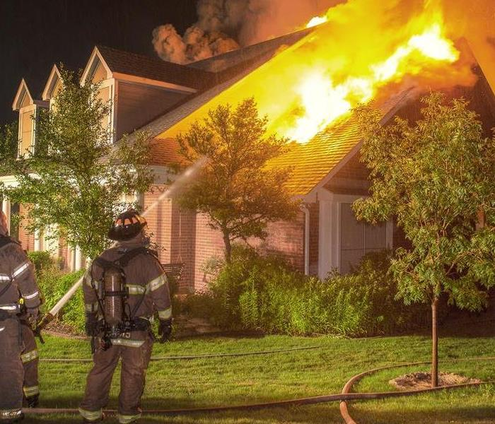 House fire with firefighters extinguishes with water hose
